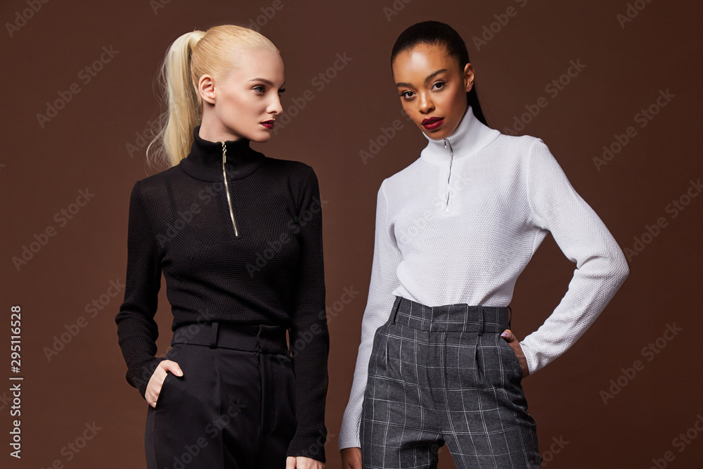 Fototapeta Two beautiful sexy woman long brunette blond hair glamour model wear pants and sweater work office style dress code accessory jewelry studio background fashion party meeting date makeup cosmetic.
