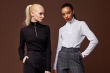 Two Beautiful Sexy Woman Long Brunette Blond Hair Glamour Model Wear Pants And Sweater Work Office Style Dress Code Accessory Jewelry Studio Background Fashion Party Meeting Date Makeup Cosmetic.