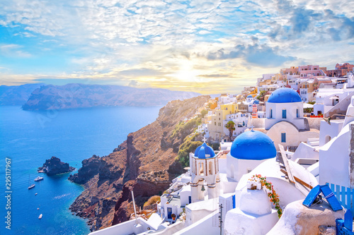 Fototapeta Beautiful Oia town on Santorini island, Greece. Traditional white architecture  and greek orthodox churches with blue domes over the Caldera, Aegean sea. Scenic travel background. obraz