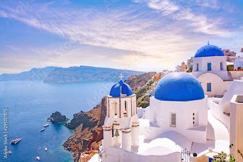 Poster Santorini Beautiful Oia town on Santorini island, Greece. Traditional white architecture and greek orthodox churches with blue domes over the Caldera, Aegean sea. Scenic travel background.