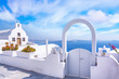 Leinwanddruck Bild - Traditional white architecture and door overlooking the Mediterranean sea in Oia Village on Santorini Island, Greece. Scenic travel background.