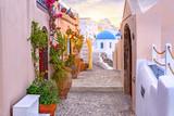 Fototapeta Uliczki - Narrow scenic street of Oia Village on Santorini Island at sunset, Greece.