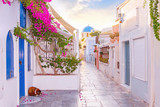 Fototapeta Uliczki - Narrow scenic street of Oia Village on Santorini Island at sunset, Greece.