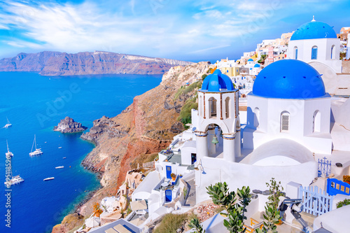 Fototapeta Beautiful Oia town on Santorini island, Greece. Traditional white architecture  and greek orthodox churches with blue domes over the Caldera in Aegean sea, Greece. Scenic travel background. obraz