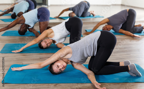 Group of active adult women and men exercising stretching workout - 295119594