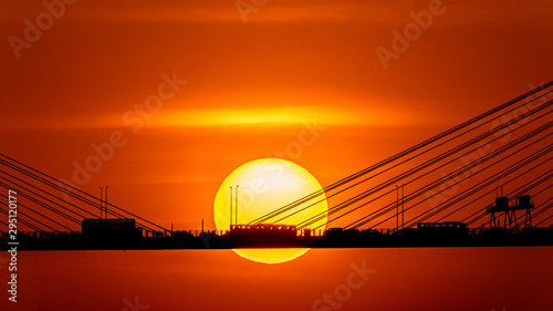 Poster de jardin Rouge traffic Sunset over the cable-stayed bridge with silhouette of car crossing the sea bay