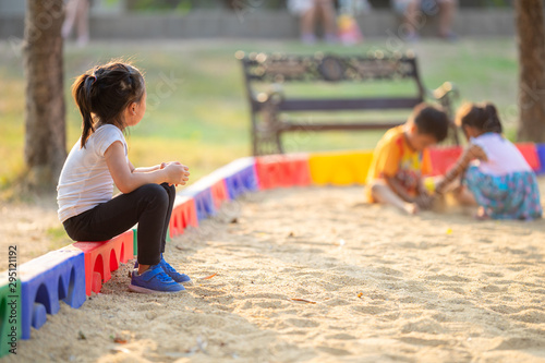 Little girl sitting lonely watching friends play at the playground Wallpaper Mural