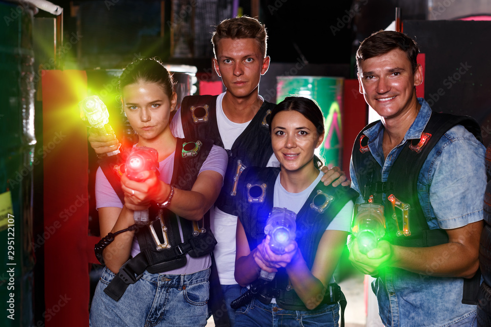 Fototapety, obrazy: Young girls and guy standing with laser guns during laser tag ga