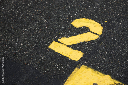 yellow number two isolated road sign painted on asphalt for background, motor race start number