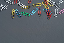 Many Scattered Different Colors Paper Clips Red, Green, Blue, Yellow, White And Pink For Office Work Or Education Lies On Dark Scratched Concrete Table. Space For Text. Top View