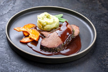 Traditional Roasted Beef Heart With Fried Pumpkin Slices And Mashed Potatoes In Gravy Red Wine Sauce As Closeup On A Modern Design Plate