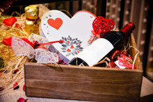 Closeup Of Red Wine Bottle With Red Ribbon And Candies Placed In Wooden Box Gift