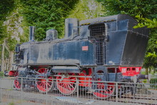 Vintage Black And Red Steam Locomotive, Which Stands In An Open Area Behind The Fence (in The Park)