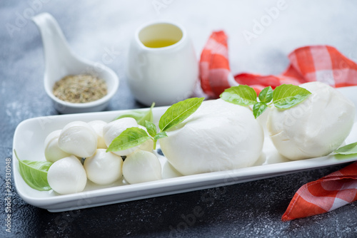 Fototapeta Closeup of mozzarella balls of defferent sizes with olive oil and green basil leaves, selective focus obraz