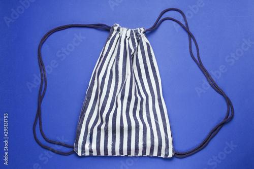 Obraz Striped beach backpack on blue background. Top view - fototapety do salonu