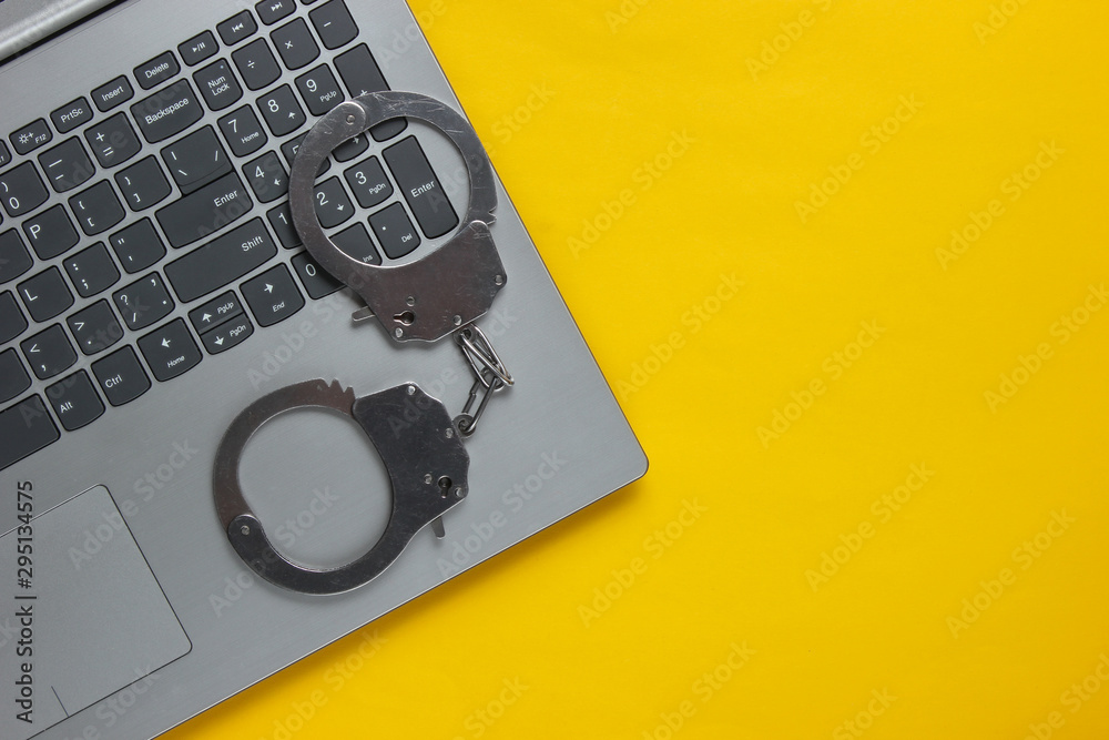 Fototapeta Cybercrime, online digital theft. Laptop with steel handcuffs on yellow background. Top view