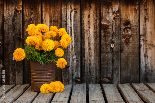 Rusty can filled with a bunch of bright orange marigold flowers next to three marigolds on a rustic plank table with room for copy