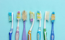Old Used Toothbrushes On Blue Background. Dental Care Concept. Top View