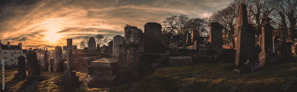 Fototapety, obrazy: EDINBURGH, SCOTLAND DECEMBER 14, 2018: old, desolated and grungy tombstones, memorials and headstones in the graveyard with the sun rising at New Calton Burial Ground