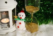A Small Toy Snowman Sits Benea...