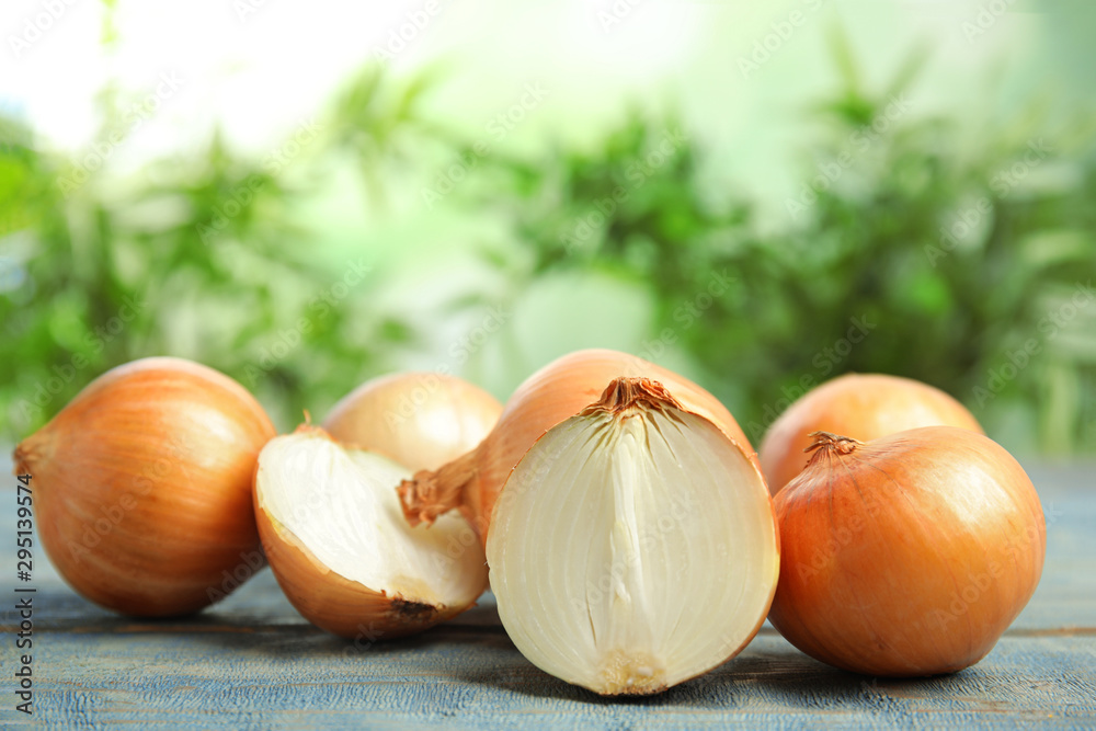Fototapety, obrazy: Ripe onions on blue wooden table against blurred background, space for text