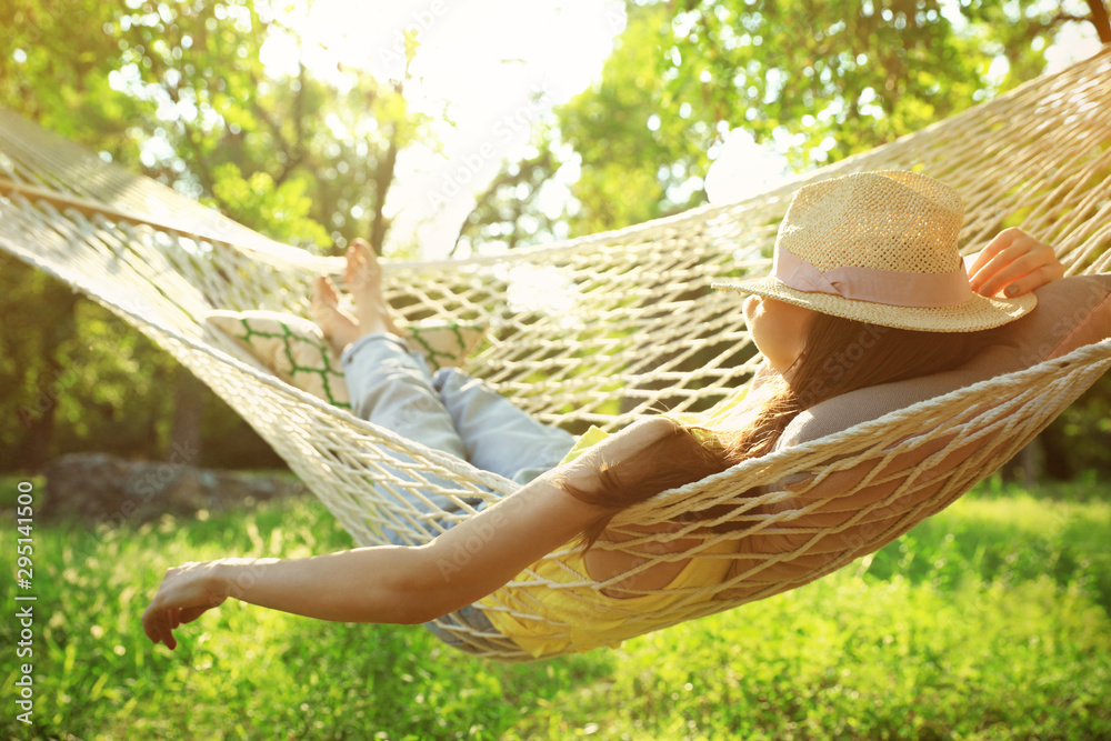 Fototapeta Young woman with hat resting in comfortable hammock at green garden