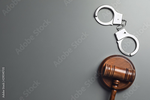 Cuadros en Lienzo  Judge's gavel and handcuffs on grey background, flat lay with space for text