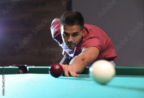 Fototapeta  Handsome young man playing Russian billiard indoors