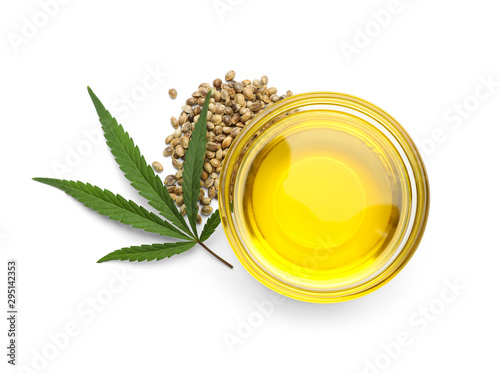 Obraz Bowl with hemp oil, leaf and seeds on white background, top view - fototapety do salonu
