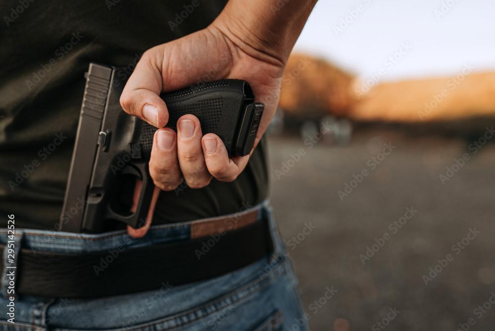 Fototapeta Man holding hidden short gun in his hand.
