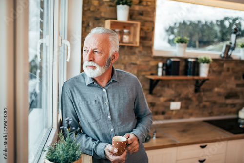 Portrait of a senior man standing in the kitchen and looking through window, holding a cup of coffee or tea on winter day Fototapet