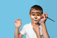 Artist Painting Face Of Little Boy On Blue Background