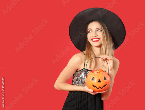 Fototapeta  Beautiful woman wearing witch costume with Jack O'Lantern candy container on red background, space for text