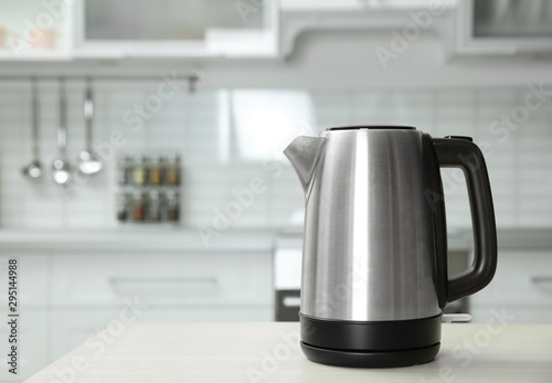Photo  Modern electric kettle on wooden table in kitchen. Space for text