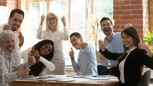Obraz Excited diverse colleagues show thumbs up gathering at meeting - fototapety do salonu