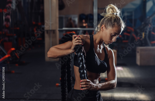 Canvastavla  Young sport woman in sportswear is training with battle rope on her shoulders in the gym