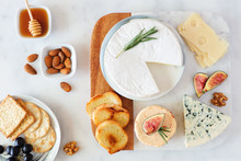 Cheese Platter With A Selection A Cheeses, Crackers, Figs, Nuts And Honey. Overhead Table Scene On A Bright Background.