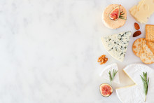 Border Of A Selection Of Cheeses, Figs, Nuts And Crackers. Top View On A White Marble Background With Copy Space.