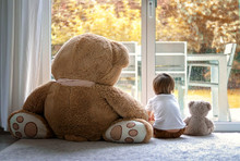 Watching Autumn Rain. Little Boy Sitting With His Big And Little Soft Teddy Bear Friends On Carpet In Front Of Window Looking Outside. Fall Lifestyle. Frendship. Seasonal Mood