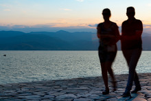 Silhouettes Of Couple Blurred In Motion As They Walk With Sun Behind.