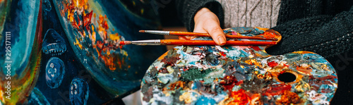 Obraz Modern fine art school. Female painter holding colorful palette and paintbrushes over abstract artwork. - fototapety do salonu