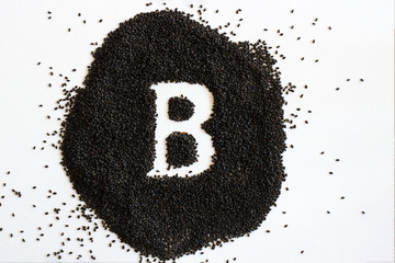 Handful of sweet basil black seeds, letter B uppercase of English alphabet on white background. Black and white. Lettering. Typography. Healthy and super food. Horizontal