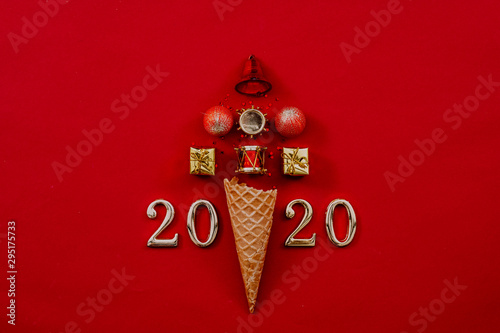 Happy New Year 2020. Abstract Christmas tree arrangement in ice cream waffle cone and numbers on maroon background. Copy space. - 295175733