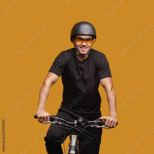 Photo Young man in black clothes and a bicycle helmet and glasses posing while sitting on a bicycle
