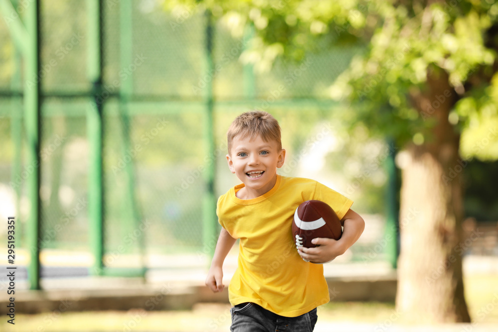 Fototapety, obrazy: Running little boy with rugby ball in park