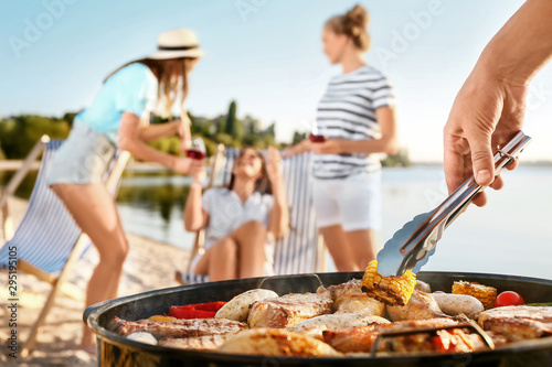 Fotografía  Man cooking tasty food on barbecue grill outdoors, closeup
