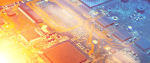 Closeup On Electronic Motherboard In Hardware Repair Shop, Blurred Panoramic Image With Details Of The Circuitry And Close-up On Electronics. Picture Toned In Orange And Blue.