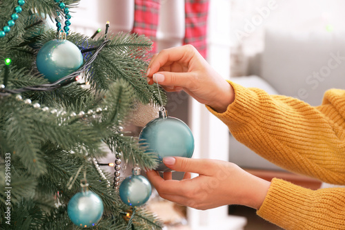 Fototapeta Woman decorating Christmas tree at home obraz