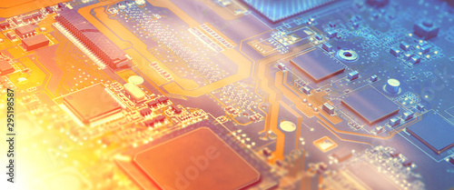 Obraz Closeup on electronic motherboard in hardware repair shop, blurred panoramic image with details of the circuitry and close-up on electronics. Picture toned in orange and blue. - fototapety do salonu