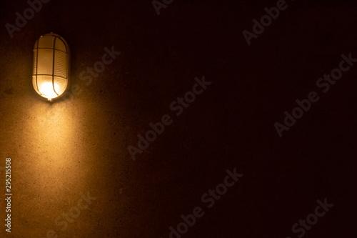 Spoed Foto op Canvas Licht, schaduw warm light bulb at wall in dark room. horizontal picture .